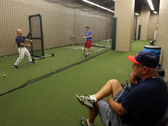 Mike Bianco pitches to son Ben in the batting cage at the College World Series as his father Ron watches.