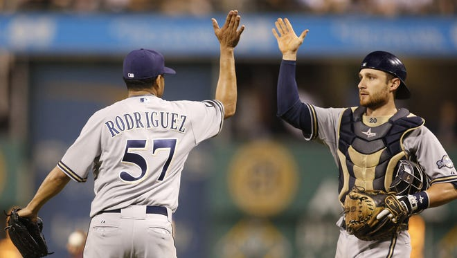 Milwaukee Brewers relief pitcher Francisco Rodriguez (57) and catcher Jonathan Lucroy (R) high-five after defeating the  Pittsburgh Pirates at PNC Park in Pittsburgh on Sept. 20, 2014.