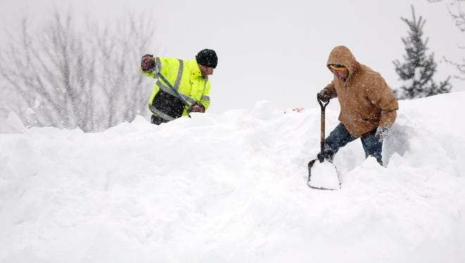Mark Settlemyer, left, gets help clearing snow from the roof of his mother's house from Ken Wesley on Nov. 19, 2014, in Lancaster.