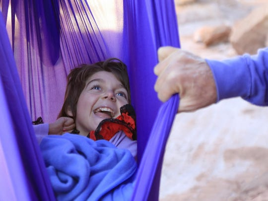 Zelah Farrell, 10, smiles at her father, Russell Farrell, as she swings from a hammock made of aerial fabric in a canyon near Zion National Park.