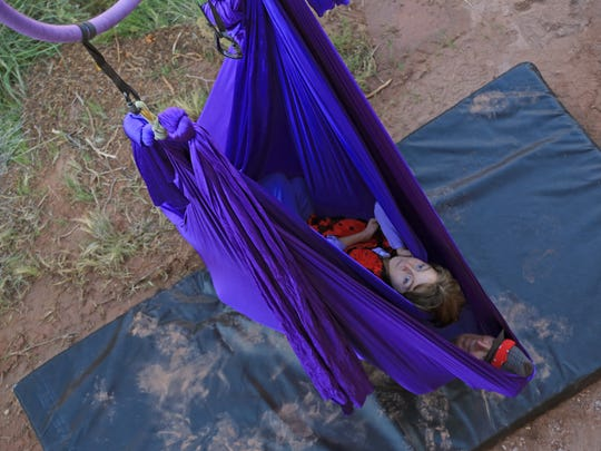 Zelah Farrell swings in a hammock made from aerial fabric in a canyon near Zion National Park above her father, Russell Farrell.