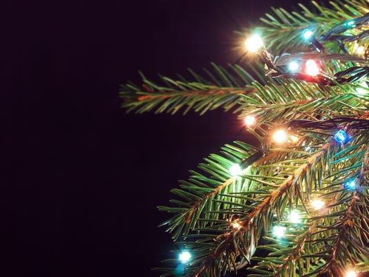 Christmas tree decked with glowing garland on a dark background