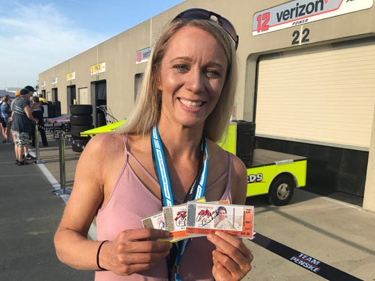 Danielle Davis holds three ticket stubs signed by Rick Mears.