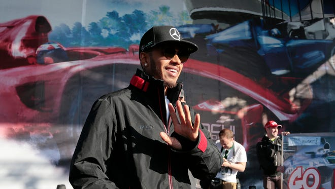 Lewis Hamilton gestures to supporters during an autograph session with fans at the 'Sochi Autodrom' circuit, Thursday.