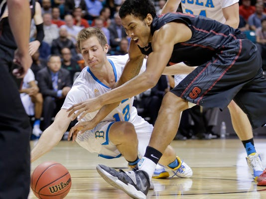 UCLA's David Wear, left, and Stanford's Josh Huestis scramble for a loose ball in the first half during an NCAA college basketball game in the semifinals of the Pac-12 men's tournament, Friday, March 14, 2014, in Las Vegas. (AP Photo/Julie Jacobson)