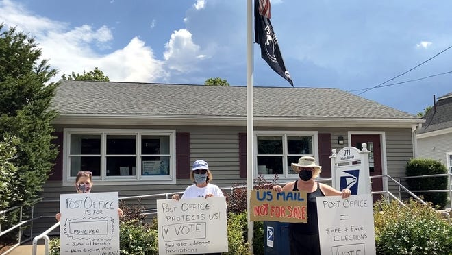 Members of Nashoba Valley Climate Coalition protested at the post office, to protect the post office, last weekend. HOlding signs are (from left) Heidi Horton Petri, Natascha Finnerty and  Rebecca Young Jones.