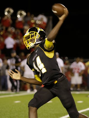 Loureauville quarterback A'Zyrian Alexander looks for an open receiver in the Catholic New Iberia defense during the second quarter of Catholic's game with Loreauville on Friday night in Loreauville.