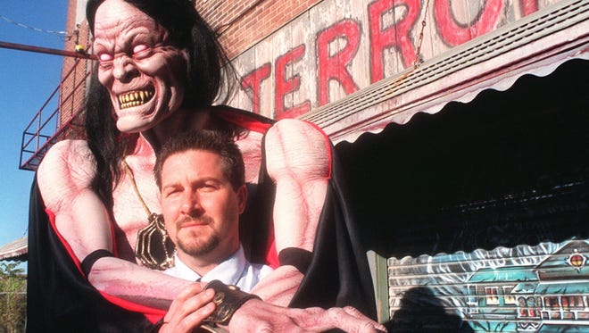 With a monster behind him, Sterling Mathis, owner of Hotel of Terror, is shown in a 1999 file photo.
