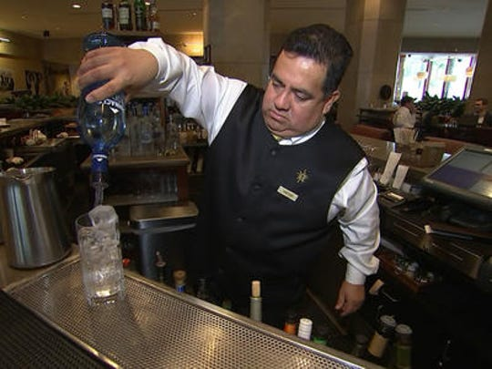 This Jan. 3, 2017 image taken from video shows Beverly Hilton hotel bartender Oscar Zuleta mixing drinks at the hotel in Beverly Hills, Calif. Zuleta has toasted with Sean Connery, gotten a head rub from Tom Hanks, shared a selfie with Jessica Alba while working previous Golden Globe Awards. The 48-year-old hotel staffer keeps the drinks flowing at the awards circuit's booziest gathering.