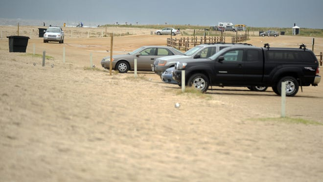 Vehicles dot the beach parking lot at Assateague National Seashore. The final version of a management plan for Chincoteague National Wildlife Refuge includes a proposal to relocate the recreational beach on Assateague Island.