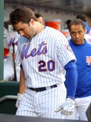 Mets second baseman Neil Walker (20) leaves the dugout into the locker room with trainer Ray Ramirez after sustaining a leg injury while running out a ground ball against the Chicago Cubs during the third inning at Citi Field on Wednesday, June 14, 2017.