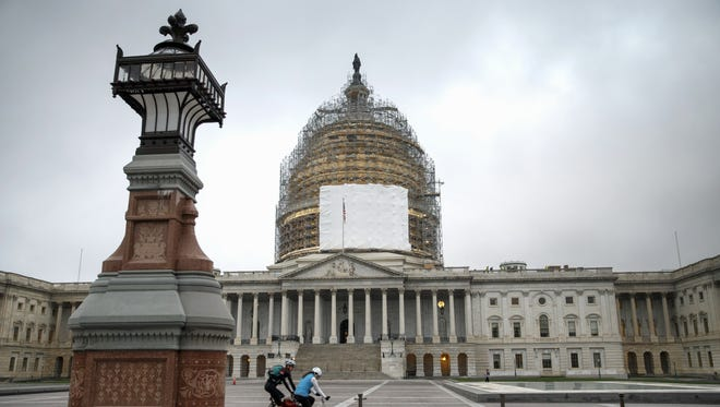 In this Nov. 12, 2014, file photo, cyclists ride past the U.S. Capitol.