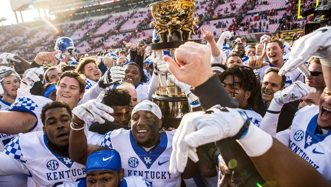The University of Kentucky football team celebrates with the Governor's Cup trophy following a 41-38 victory over U of L at Papa John's Cardinal Stadium on Saturday. Nov. 26, 2016