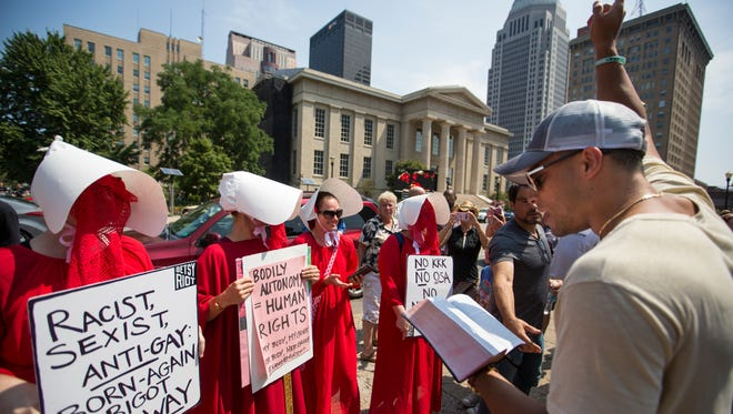 Nelson Villaverte, right, read from the bible in front of women dressed as handmaids during a confrontation between anti-abortion and pro-abortion rights advocates at Jefferson Square Park, in Louisville. July 26, 2017.