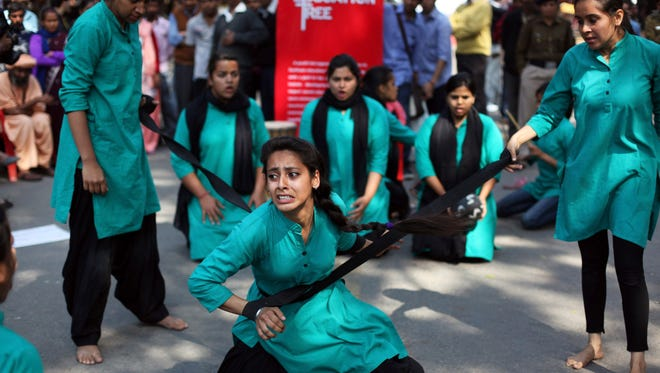 A group of college girls perform a street play on violence against women, to mark International Women's Day in New Delhi, India, Saturday, March 8, 2014.