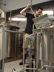 Andrew Harton, Big Oyster Brewery's head brewer, stirs a batch of beer.