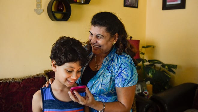 Ragaa Thabet laughs as she helps her son Mena Thomas, 8, speak Egyptian to relatives on the phone in their York home. Thabet and her husband, Hany Thomas, came to the U.S. in 2009 so that they raise their children away from the religious persecution they faced in Egypt.