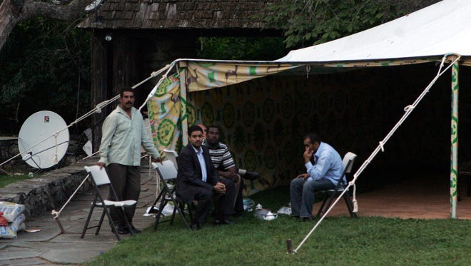 Men stand around a tent on the grounds of Seven Springs estate off Oregon Road in Bedford  Sept. 24, 2009. The Libyan government has pitched a tent on the property that leader Moammar Gadhafi may use for entertaining, according to a State Department official.