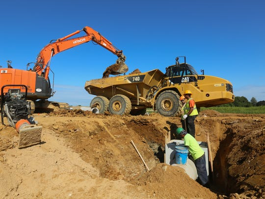 Construction workers install pipes along U.S. 301.