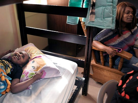 Kennedy Washington,7, lays in her bed while laughing