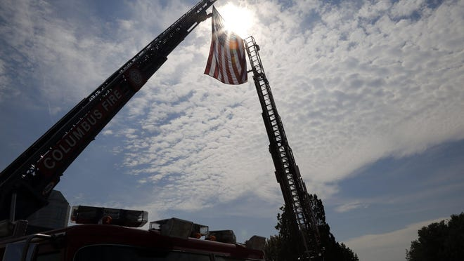 Columbus Fire trucks hoist an American Flag over Broad Street during a 9/11 remembrance ceremony at the National Veterans Memorial and Museum in Columbus on Wednesday, Sept. 11, 2019. The ceremony honored the victims and the first responders who were affected by the terrorist attacks 18 years ago.