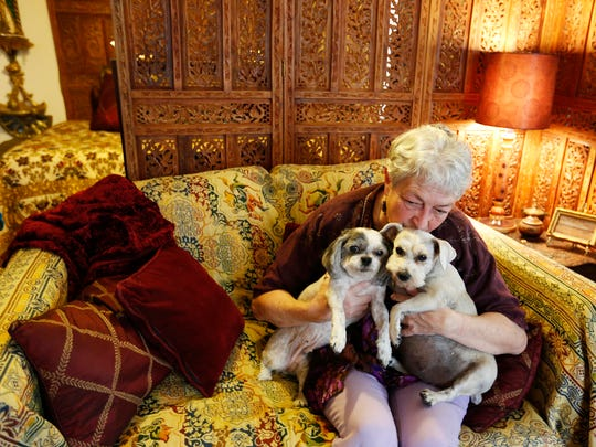 In this Nov. 29, 2017 photo, Bette Cyr gives attention to her dogs Sissy and Cassie at her home in Crawford, Colo. Cyr adopted her dogs from Debbie Faulkner,owner of the Black Canyon Animal Sanctuary and founder of the Silver Whiskers program where senior pets are paired with senior citizens.