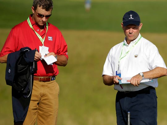 Golf architect and Gil Hanse takes notes with USGA President Mike Davis on the 18th green before Davis uses a level to measure the roll on a certain part of the green, presumably for determining cup placement during the practice for the  2017 U.S. Open  Championship at Erin Hills.