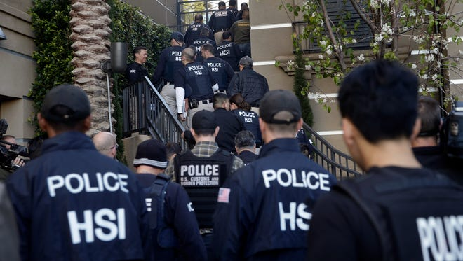 Federal agents enter an upscale apartment complex March 3, 2015, in Irvine, Calif. Shortly after sunrise, federal agents swarmed the complex in the Orange County where authorities say a birth tourism business charged pregnant women $50,000 for lodging, food and transportation. The key draw for travelers is that the United States offers birthright citizenship.
