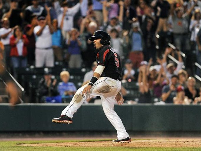 Rochester's Eric Farris celebrates his game-winning run, scoring from second on a single by teammate Nate Hanson during regular season game played at Frontier Field on Saturday, July 26, 2014.  The Red Wings scored the game's only run in the bottom of the ninth inning to beat the Indianapolis Indians 1-0.