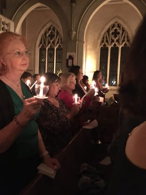 Women attending First United Methodist Church of San Angelo's Advent candlelight service for women hold their lit candles at the service's conclusion.