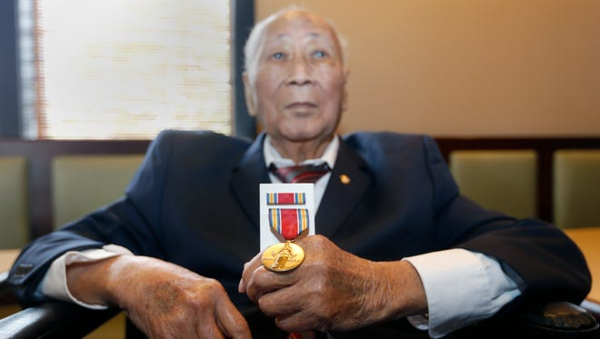 World War II Army Veteran David Leong sits holding his World War II Victory Medal that he was presented by U.S. Rep Billy Long on Friday, May 20, 2016. Leong lost his medals during a harrowing escape from China in 1945, according to his son, Wing Wah Leong.