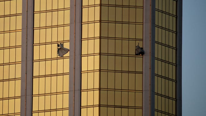 FILE - In this Monday, Oct. 2, 2017 file photo, drapes billow out of broken windows at the Mandalay Bay resort and casino on the Las Vegas Strip, following a mass shooting at a music festival in Las Vegas. From two broken-out windows of the resort, Stephen Craig Paddock had an unobstructed view to rain automatic gunfire on the crowd, with few places for them to hide. Sunday night's bloodbath left dozens of people dead and hundreds wounded. (AP Photo/John Locher, File) ORG XMIT: NYR301