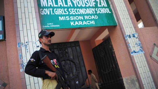 A Pakistani policeman stands guard in front of the Malala Yousafzai  Girl's School in Karachi on Friday.