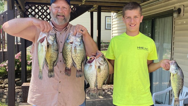 From left, Topekan Marty Reddick and his grandson, Braden, hold up several 14- and 15-inch crappie they caught from a Jefferson County farm pond last week.