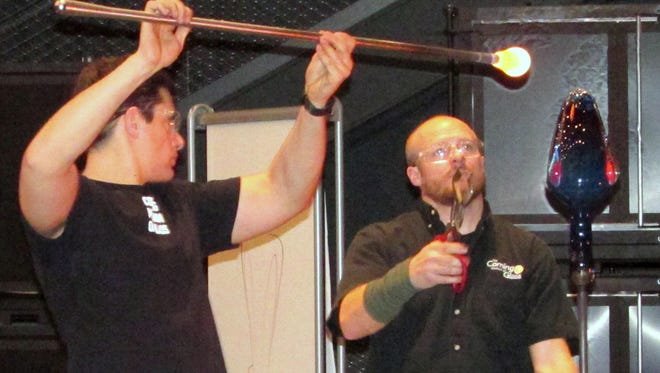 Corning Museum of Glass gaffer G Brian Juk, right, and assistant Tom Ryder create a glass ornament during the hot glass show Wednesday at the museum.