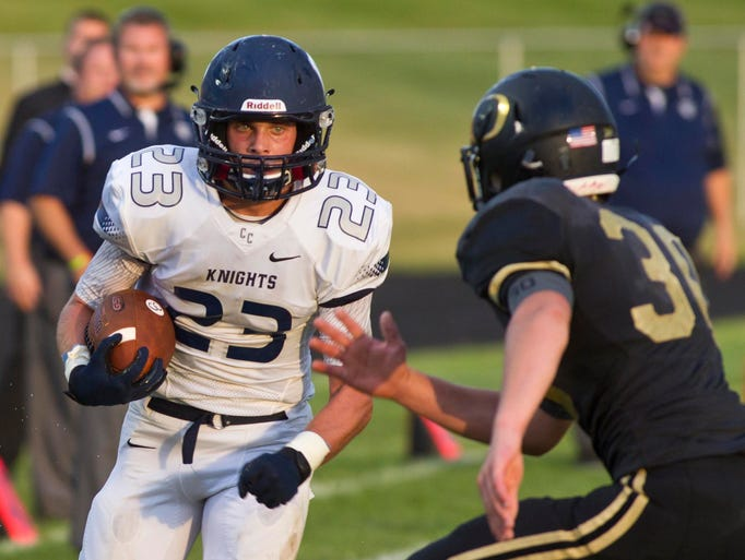 Central Catholic running back Jackson Anthrop eyes Delphi's Treavor Cox on a run Friday, August 22, 2014 at Berto Field in Delphi.