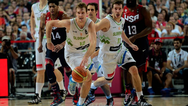 Slovenia's Zoran Dragic, with ball, and brother Goran (No. 11) head up court during the Basketball World Cup quarterfinal against the U.S in Barcelona, Tuesday, Sept. 9, 2014.