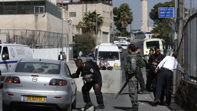 Israeli security personnel check Palestinian pedestrians and vehicles at a newly installed road block in the Palestinian neighbourhood of Ras al-Amud in east Jerusalem, on October 15, 2015.