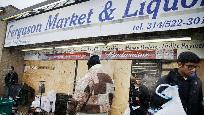 In this Wednesday, Nov. 26, 2014, file photo, Kush Patel, right, carries out bags of merchandise while helping his uncle Andy Patel, rear, clean up the looting damage from Monday's riots at his store, Ferguson Market and Liquor, in Ferguson, Mo. The store is disputing a new documentary's claims that surveillance video suggests Michael Brown didn't rob the store before he was fatally shot by police in Ferguson. One of the filmmakers said he believes the footage shows Brown trading marijuana for a bag of cigarillos early on Aug. 9, 2014, and that Brown intended to come back later for the cigarillos. Store officials said no drug transaction took place and Brown stole the cigarillos while at the store later that day.