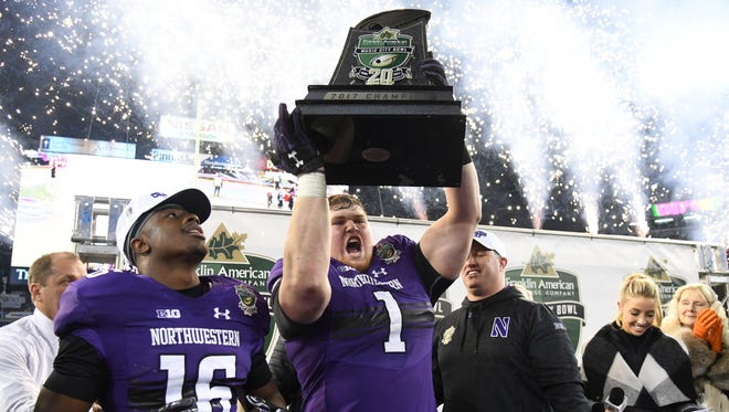 Northwestern Wildcats defensive lineman Tyler Lancaster (1) and safety Godwin Igwebuike (16) celebrate with the Music City Bowl trophy following a win against the Kentucky Wildcats at Nissan Stadium.