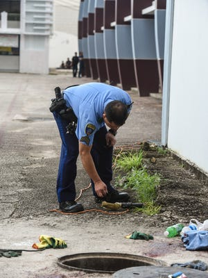 Guam Police Department officers investigate an auto-pedestrian incident at the old Hafa Adai Exchange in Tamuning on Tuesday, Jan. 17, 2017. A plumber's helper, employed by Inland Builders Corp., was found seriously injured while partially remaining in a manhole, by co-worker Johnny Teopaco. Teopaco said he had momentarily stepped away from the manhole.