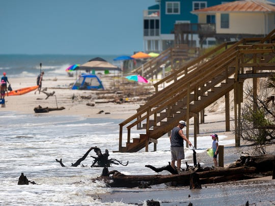 Beachgoers negotiate erosion damage caused by a strong