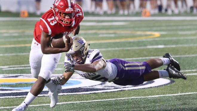 Seabreeze High's Tashod Troutman #23 slips atackle by Winter Springs JJ Contreras#25, Thursday September 19, 2019.