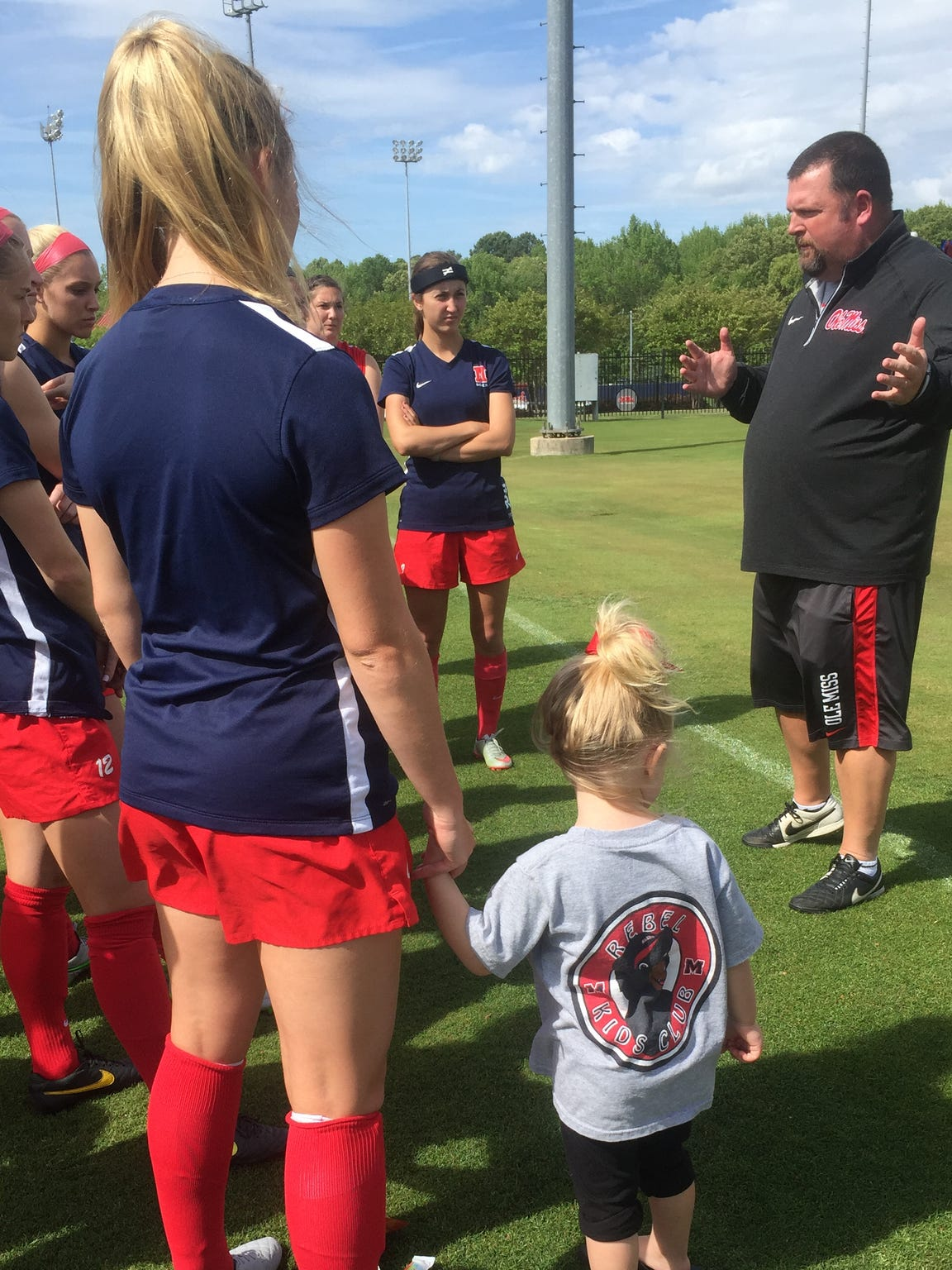 Sara Coleman attends practice while holding her daughter's hand.