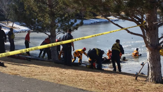 Rescue crews pull a teen boy from a frozen pond in south Reno on Thursday afternoon.