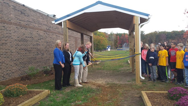 Millside Elementary Principal Melissa Hanners, Algonac Rotary President Amber Voigt, student Mia Pellegata and United Way Executive Director Doug Dolph cut the ribbon to the outdoor classroom at Algonquin Elementary School.
