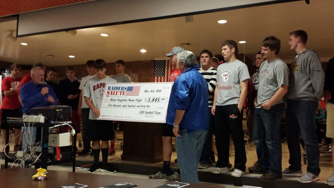 """The Lincoln High School football team presented a donation for $5,845 to Jim Campbell and Mike Thompson, co-founders of the Never Forgotten Honor Flight, during its banquet Wednesday. Campbell and Thompson told the team the donation would send about 11 veterans on the trip to Washington, D.C., to visit the memorials created to honor World War II, Korean and Vietnam veterans. The team sold """"Raider Salute"""" T-shirts to raise funds for the Honor Flight, and donations also were accepted at its Oct. 16 game. During that game the American Legion Riders also presented the Colors."""