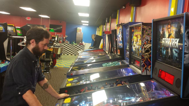 Yestercades, closed for four months after a roofing problem,is re-opening this weekend. Assistant manager Christian Murray checks out a pinball machine.