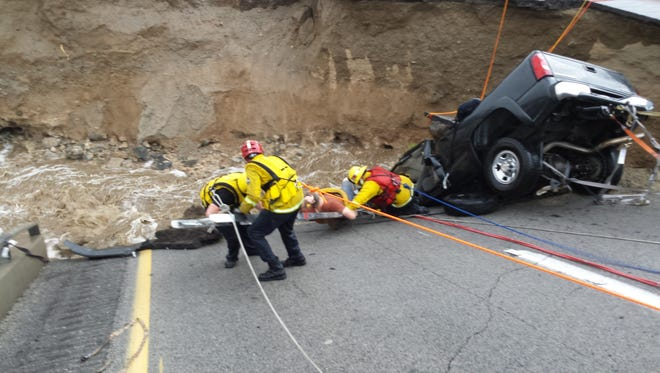 Firefighters work to rescue a pinned motorist from a stranded truck after the Tex Wash Bridge collapse.