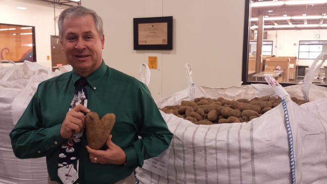 New Mexico Secretary of Agriculture Jeff Witte stands next to a tote of New Mexico-grown potatoes, donated to Roadrunner Food Bank by Navajo Agricultural Products Industry.
